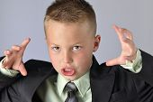 stock photo of contortion  - Closeup of young Caucasian boy in business suit making face and gesturing with hands as if he is going to attack - JPG
