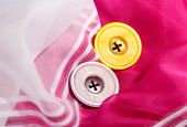 Two buttons on pink and white cloth