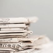 Pile of black and white newspapers on a wooden table