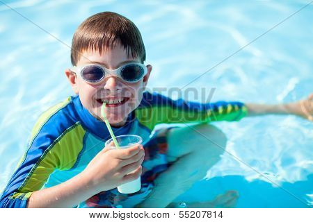 Cute boy at all inclusive resort swimming pool sipping cocktail