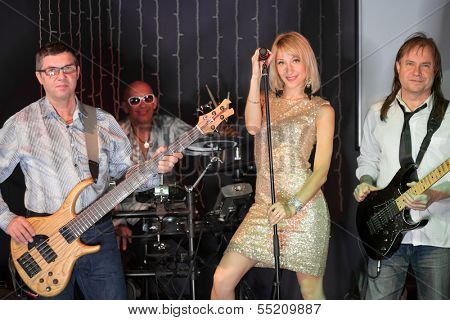 The musical group of three men and one girl performs  on stage in a club