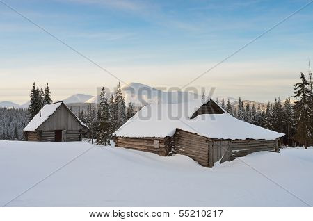 Winter landscape at sunrise with mountain huts in the snowdrifts. Carpathian Mountains, Ukraine, Europe