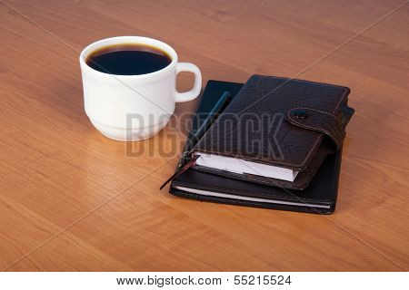 Ball pen, organizer and cup of coffee