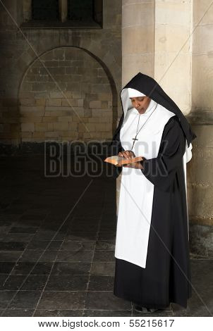 Nun in habit reading the bible in a medieval church
