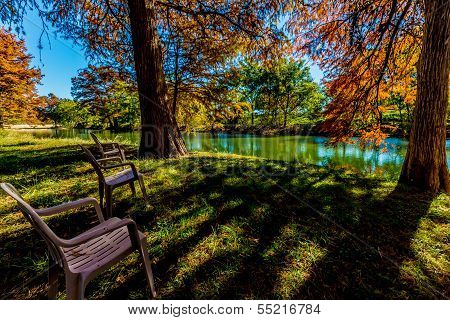 Relaxing Lawn Chairs with Beautiful Fall Foliage On The Guadalupe River, Texas.