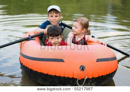Three children float on a rubber boat with oars, focus on little boy.
