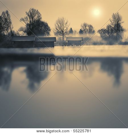 Boathouses on a lake in winter with fog and sun