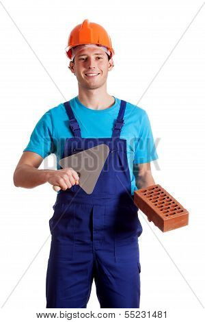 Young Constructor With Putty Knife And Brick