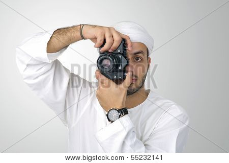 Young Arabian man using holding his camera ready to shoot, isolated