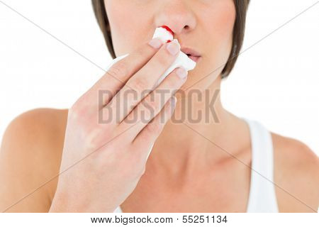 Close-up mid section of a young woman with bleeding nose over white background