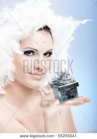 Attractive winter girl holding small present box, wearing professional makeup with strasses and white feather hat.