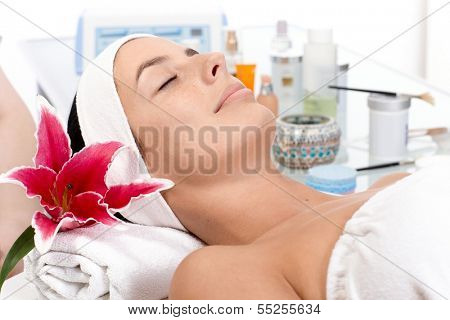 Young female relaxing eyes closed in beauty parlour, receiving treatment.