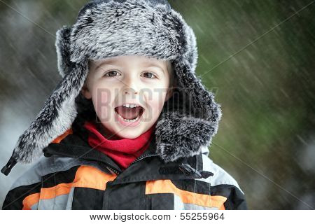 Three year old boy having fun in the outdoor Winter cold and snow
