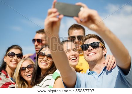 summer, holidays, vacation and happiness concept - group of friends taking picture with smartphone