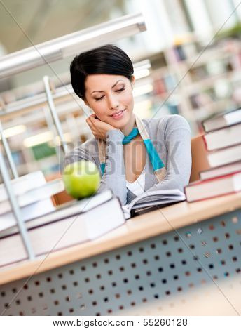 Female student with green apple studies sitting at the desk at the reading hall of the library. Academic achievement