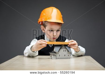 Portrait of little boy in headpiece with home model and ruler on grey background. Concept of real estate and engineering