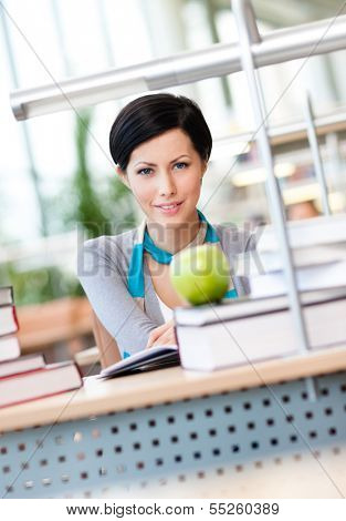 Female student with green apple studies sitting at the table at the reading hall of the library. Training concept