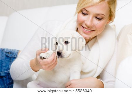 Woman is on the white leather sofa with white puppy of Labrador giving the paw