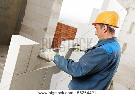 construction mason worker bricklayer installing calcium silicate brick during indoor wall creation