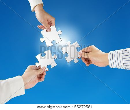 Hands hold puzzles with clear blue sky and sun light background