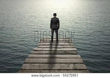 Businessman standing and thinking on old wooden pier to the sea