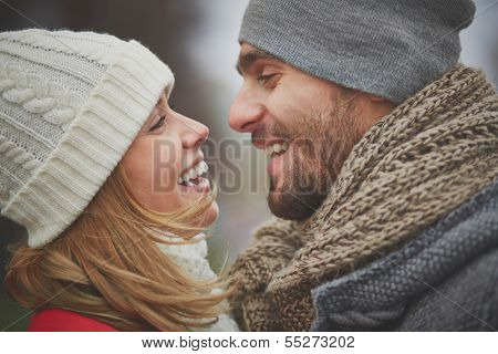 Portrait of happy guy and his girlfriend looking at one another