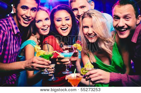 Group of happy friends with cocktails toasting at party