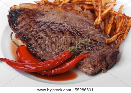 meat food : grill beef steak with potato chips and dry red hot chili peppers  on white round plate isolated on white background
