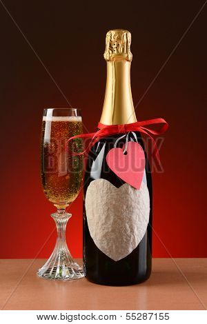 Closeup of a champagne bottle decorated for Valentines Day. A glass of champagne is next to the bottle. The bottle has a red ribbon and heart shaped tag and a blank heart shaped label.
