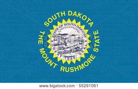 South Dakota state flag of America on brick wall, isolated on white background.