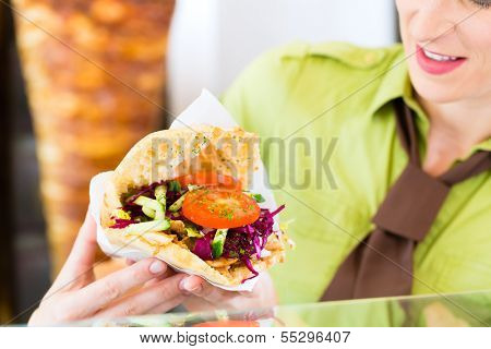 Doner kebab - friendly vendor in a Turkish fast food eatery, with a freshly made pita bread or kebab in front of skewer
