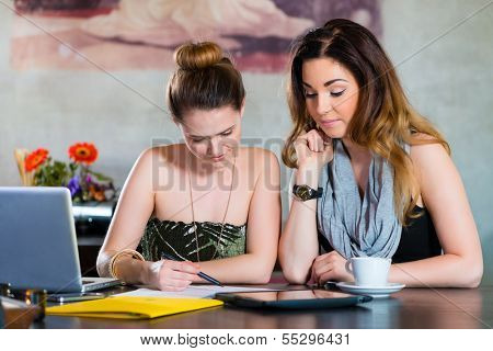 Young women or colleagues working in a cafe or restaurant, on some documents or contract