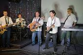 The musical group of five men in white shirts and ties performs on stage in a club