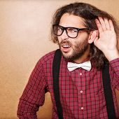stock photo of shock awe  - Emotional portrait of a guy who is trying to hear each other hipster Style studio shot - JPG