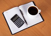 Coffee and calculator on open notebook