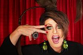 stock photo of drag-queen  - Laughing Caucasian drag queen in theater with hand near face - JPG