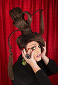 stock photo of drag-queen  - Frightened drag queen with large beetle earrings and ponytails - JPG