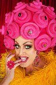 picture of drag-queen  - Grinning drag queen in plastic wig biting fingernails - JPG