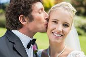 image of full cheeks  - Groom kissing his pretty blonde wife on the cheek in the countryside - JPG