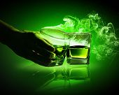 image of absinthe  - Hand holding one of two glasses of green absinth with fume going out - JPG