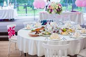 stock photo of wedding feast  - Wedding white banquet tables prepared for wedding celebration - JPG