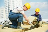 foto of insulator  - Roofer builder worker installing roof insulation material - JPG