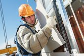 stock photo of millwright  - worker builderinstalling big tile on aerated facade constructiona of building - JPG
