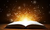 stock photo of bible story  - Old open book with magic light and falling stars on wooden table - JPG