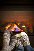 stock photo of cozy hearth  - Feet in wool socks warming by cozy fire - JPG