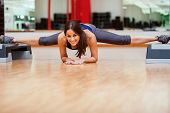 stock photo of leg-split  - Beautiful young woman playing around at a gym and doing a leg split - JPG