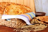 Pita breads in basket with spikes and flour on table on wooden background