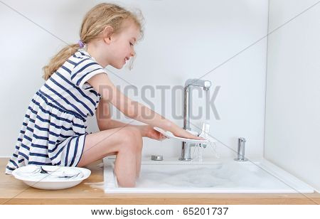 Happy Little Girl Washing The Dishes In The Kitchen.