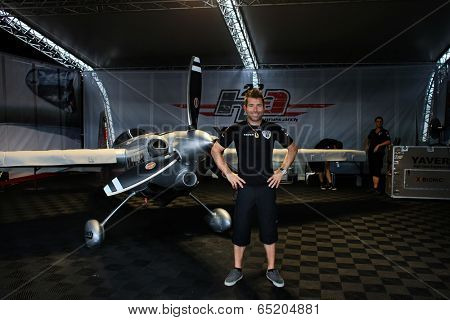 PUTRAJAYA, MALAYSIA - MAY 17, 2014: World champion Hannes Arch from Austria poses with his Edge 540 v3 plane in his hangar at the Red Bull Air Race World Championship 2014 in Putrajaya, Malaysia.