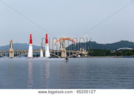 PUTRAJAYA, MALAYSIA - MAY 17, 2014: An unidentified pilot in a para-glider performs flying stunts over the lake during the breaks between races at the Red Bull Air Race World Championship 2014.